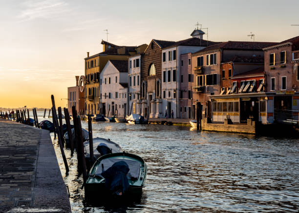 Moored boats in a Venice canal at sunset stock photo