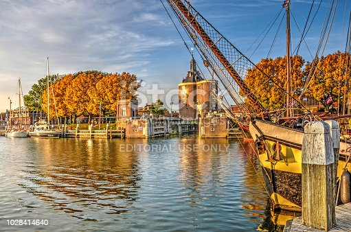 Enkhuizen, The Netherlands, October 26, 2015: historic saling yacht moored in the Buitenhaven (Outer Harbour) with Dromedaris Gate in the background