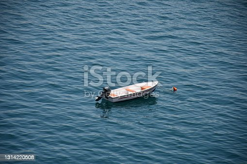 Small, empty motorboat attached to a mooring buoy in the Mediterranean Sea in Malta.