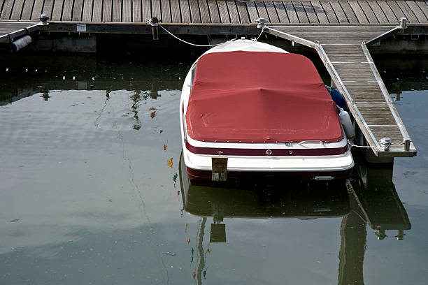 Moored motorboat with tarpaulin stock photo