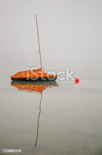 istock Moored Sailboat in the Fog With Reflection 1226952245