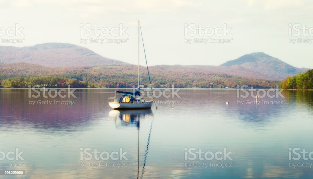Moored sailboat on New England lake foggy Autumn afternoon stock photo