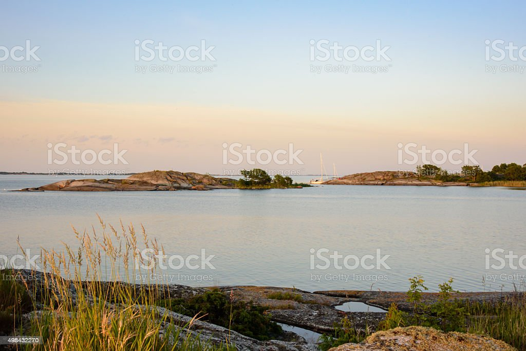Moored sailboats and skerries in sunset light stock photo