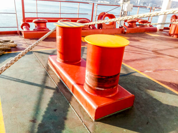 mooring bollard on the decks of an industrial seaport. - cable winch stock photos and pictures