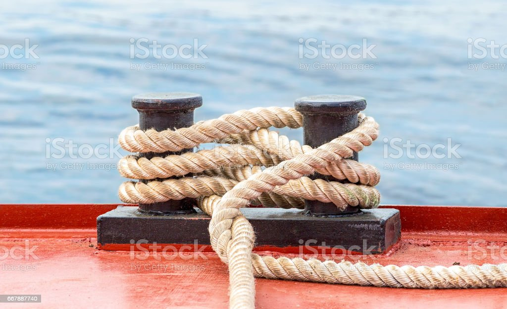 Mooring bollard with a fixed rope on the ship against the water background stock photo