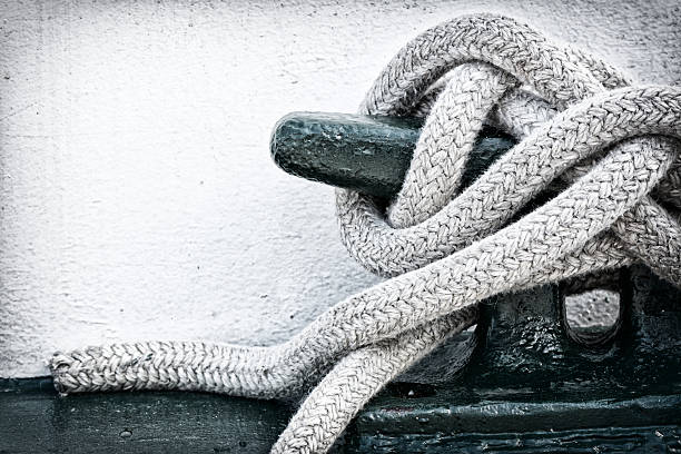 Mooring Line on Cleat A detailed closeup macro of a rope mooring line fastened to a cleat. Space for copy. mooring stock pictures, royalty-free photos & images