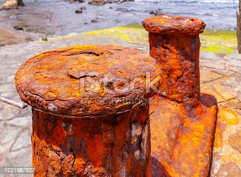 Old rusty mooring post on slipway ate the waterfront.