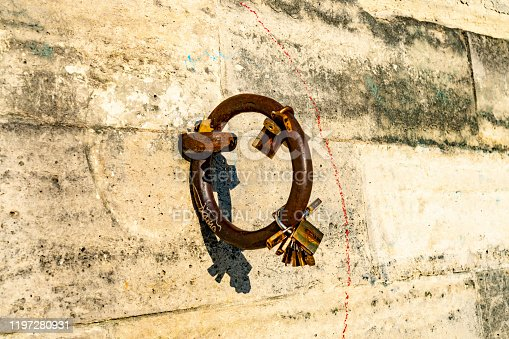 2019 Mooring ring on the embankment wall of the River Seine with a series 'memory' padlocks, with their shadows. Paris, France