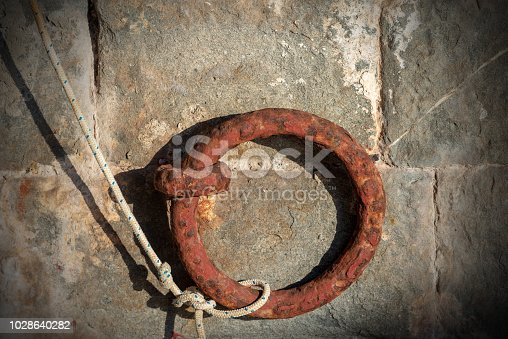Close-up of a rusty mooring ring with a white and blue rope on a wall in a port, Liguria, Italy