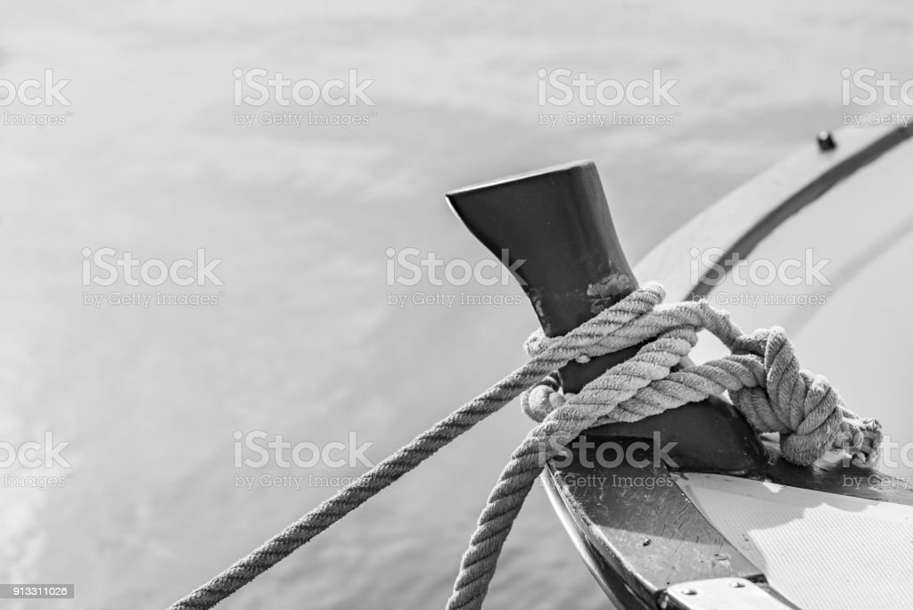 Mooring rope is knotted on boat cleat stock photo