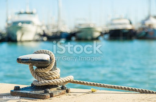 Mooring rope and bollard on sea water and yachts background