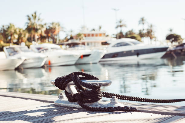 Mooring yacht rope tied around a cleat Mooring yacht rope with a knotted end tied around a cleat on a wooden pier against marina view mooring stock pictures, royalty-free photos & images