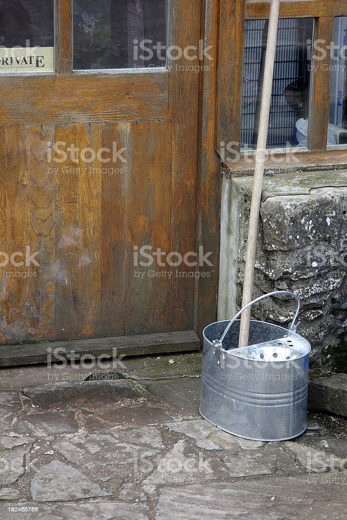 Mop and bucket outside door royalty-free stock photo