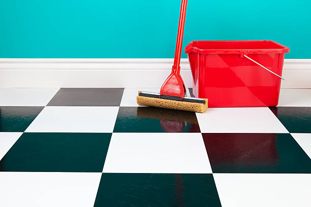 Mop and Bucket A red bucket and mop on a white and black checkered floor against a turquoise blue wall. linoleum stock pictures, royalty-free photos & images