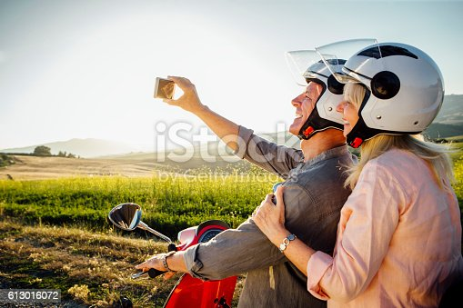 A senior couple taking a self portrait on a smart phone, they are sitting on a moped and are wearing crash helmets, ready to go off on an adventure.