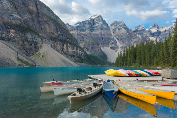 Moraine Lake and Valley of the Ten Peaks in Banff National Park Moraine Lake in Banff National Park with mountains in the background and colourful canoes in the foreground. valley of the ten peaks stock pictures, royalty-free photos & images