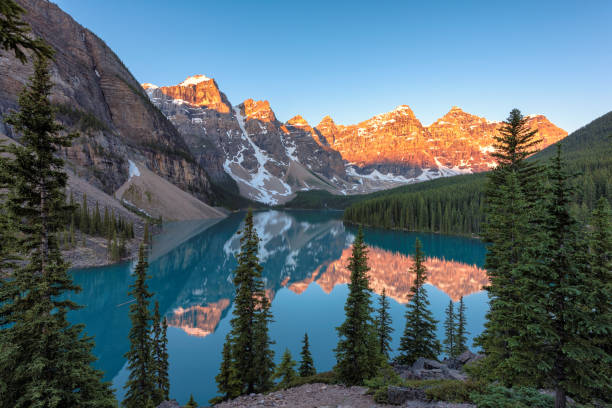 Moraine lake at sunrise in Banff National park, Alberta, Canada. Moraine Lake, Famous place in Rocky Mountains, Canada. A famous place on the anniversary of 150 years emerald lake stock pictures, royalty-free photos & images