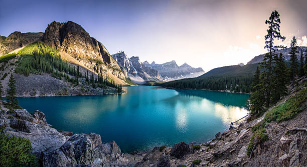 Moraine Lake at Sunset The emerald waters of Moraine Lake at sunset.  A panoramic photo. rocky mountains north america stock pictures, royalty-free photos & images