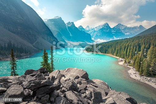 istock Moraine Lake in Banff National Park on a partly cloudy summer day. Mountain range in the back in a soft haze. Wind chases clouds across the sky. Hiking in the Canadian Rockies. 1319119939