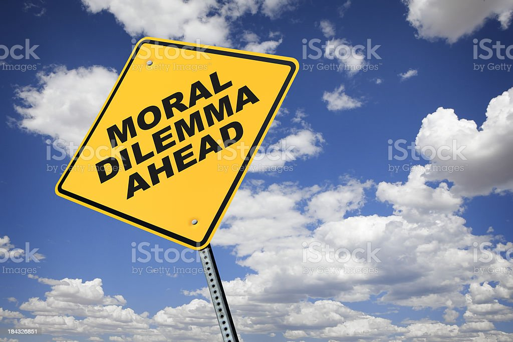Moral Dilemma road sign in front of cloud filled sky royalty-free stock photo