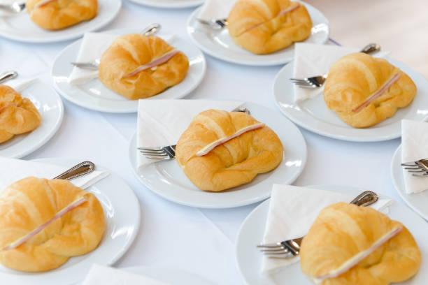 Frisches Croissant-Sandwich mit Schinken und Käse auf weißem Teller. Teezeit und Kaffeepause bei Konferenzgesprächen – Foto