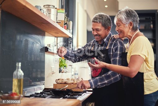 Shot of a happy mature couple adding salt to a dish while cooking together at home