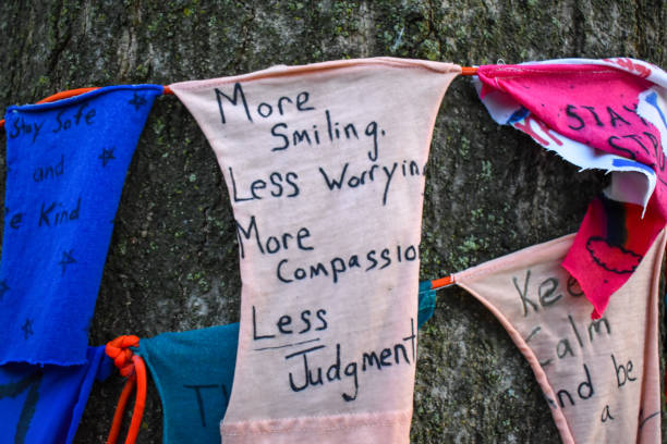 """more smiling less worrying more compassion less judgement"" written on a sign on a tree by kids for corona virus covid-19 relief westfield, nj new jersey - first responders стоковые фото и изображения"