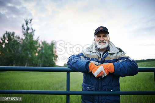 Portrait of a mature man standing at the fence of a farm