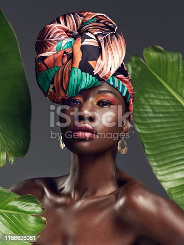 Studio shot of a beautiful young woman wearing a traditional African head wrap against a leafy background