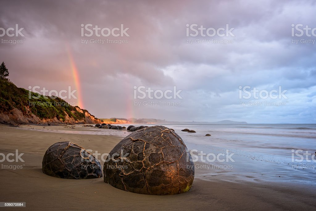 Moreaki boulders with a rainbow stock photo