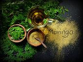Moringa Oleifera tea with powder on table written moringa wording