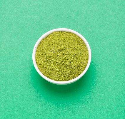 Moringa powder - Moringa oleifera. Green background