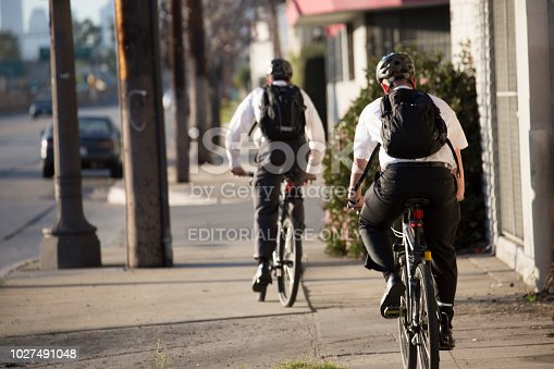 Los Angeles, CA, USA - February 3, 2013: Two Mormon missionaries ride bicycles through Los Angeles.