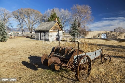 Rusted Wagon Wheel in front of old Wild West Log Cabin in Mormon Pioneer Heritage Park, Scenic Highway 89 near City of Panguitch, Utah