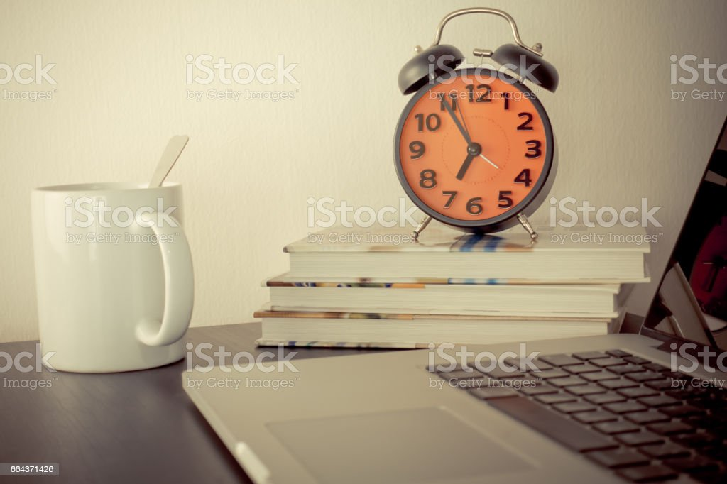 Morning Alarm Clock and coffee on office table with computer stock photo