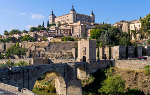 Morning at Toledo - Panoramic morning view of the historic city Toledo at Puente de Alcántara, a Roman arch bridge at front of east city gate Puerta de Alcántara and crossing over Tagus River. Toledo, Spain. stock photo
