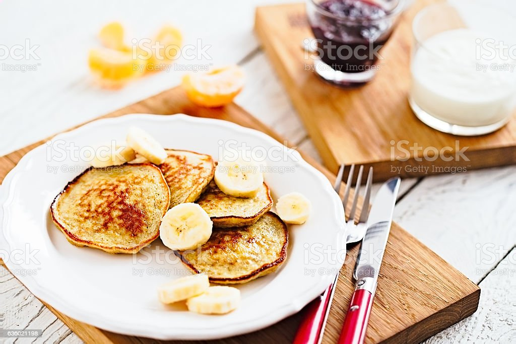 Morning banana pancakes with on white plate and wooden table stock photo