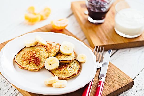 morning banana pancakes with on white plate and wooden table - gebackene banane stock-fotos und bilder
