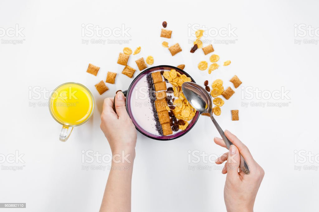 Morning breakfast. Female hands hold a spoon over a bowl with homemade yogurt and cornflakes, raisins, almonds on white background, top view, flat lay. Concept of healthy food, healthy food, detox. Copy Space stock photo