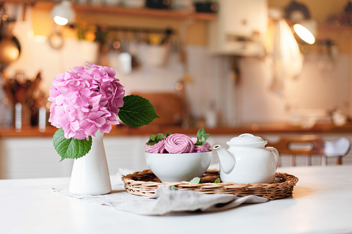 Morning breakfast on kitchen table. White teapot, pink cupcakes and hydrangea flowers are serving on straw tray. Tea time, cozy home atmosphere hygge. Summer still life with sweets.