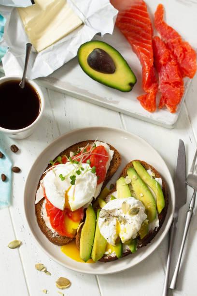 아침 식사. 다진 달걀 삶은 샌드위치와 아보카도, 연어, 커피를 나무 테이블에 얹어 드세요. 상단보기 평면 누워 배경입니다. 스톡 사진