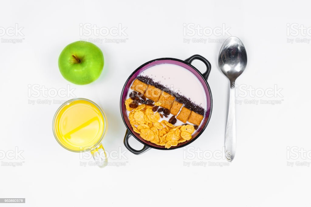 Morning breakfast. Spoon, bowl with homemade yogurt and cornflakes, raisins, almonds, green apple and orange juice on white background, top view, flat lay. Concept of healthy food, healthy food, detox. Copy Space stock photo