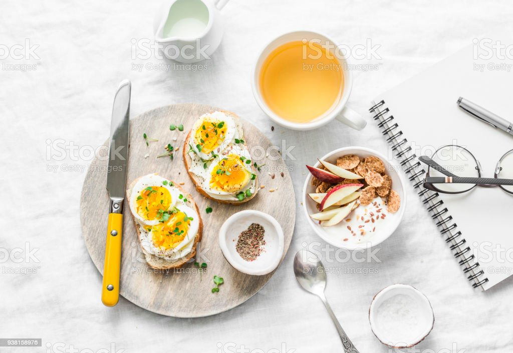 Morning breakfast table inspiration - sandwiches with cream cheese and boiled egg, yogurt with apple and flax seeds, herbal detox tea, notebook, glasses on light background, top view. Flat lay