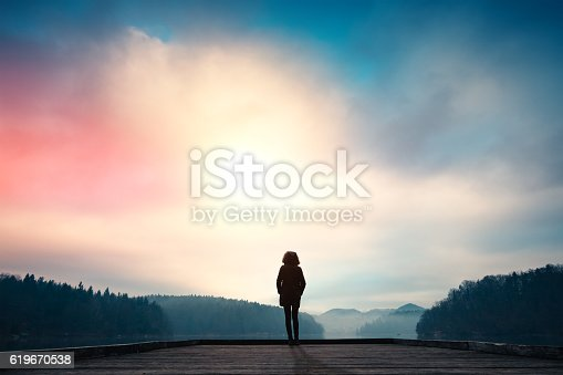 Woman standing on jetty and watching sunrise by the lake.