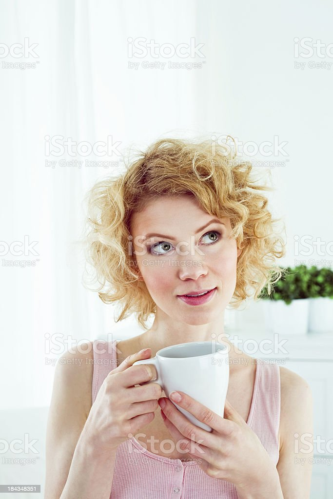 Morning caffee Pretty young adult woman wearing pink sleeveless top holding cup of coffee in the morning, looking up. 20-24 Years Stock Photo