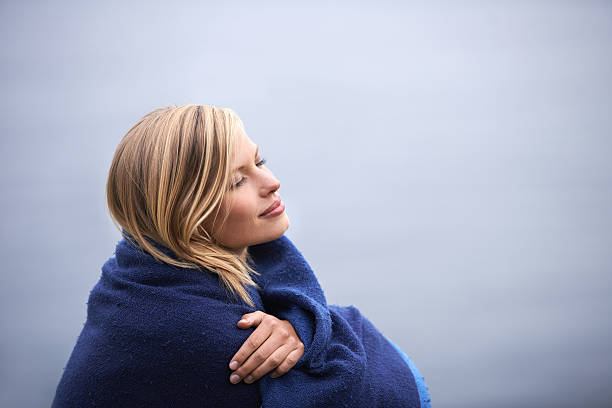 Morning calm Shot of a beautiful young woman wrapped in a blanket sitting at the ocean wrapped in a blanket stock pictures, royalty-free photos & images