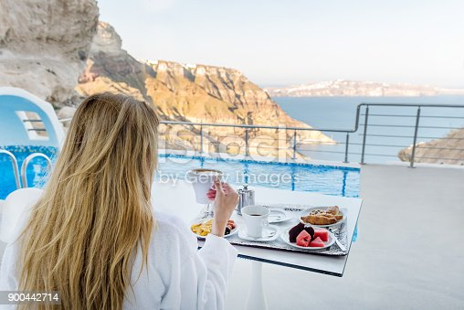 Horizontal color rear view image of pretty woman having breakfast and drinking coffee on terrace with view on Aegean sea.