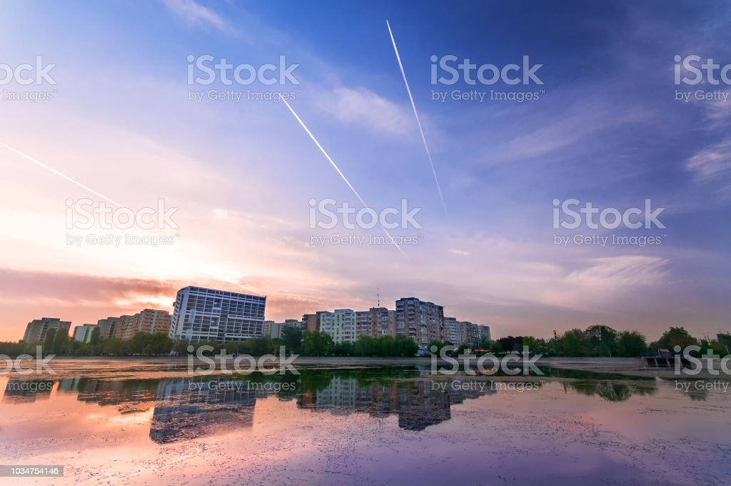 Morning cityscape at sunrise near a lake with reflection and plane streaks in the sky stock photo
