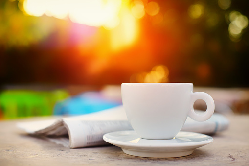 Morning coffe or tea in a white cup and a newspaper with beautiful glowing  bokeh at the background