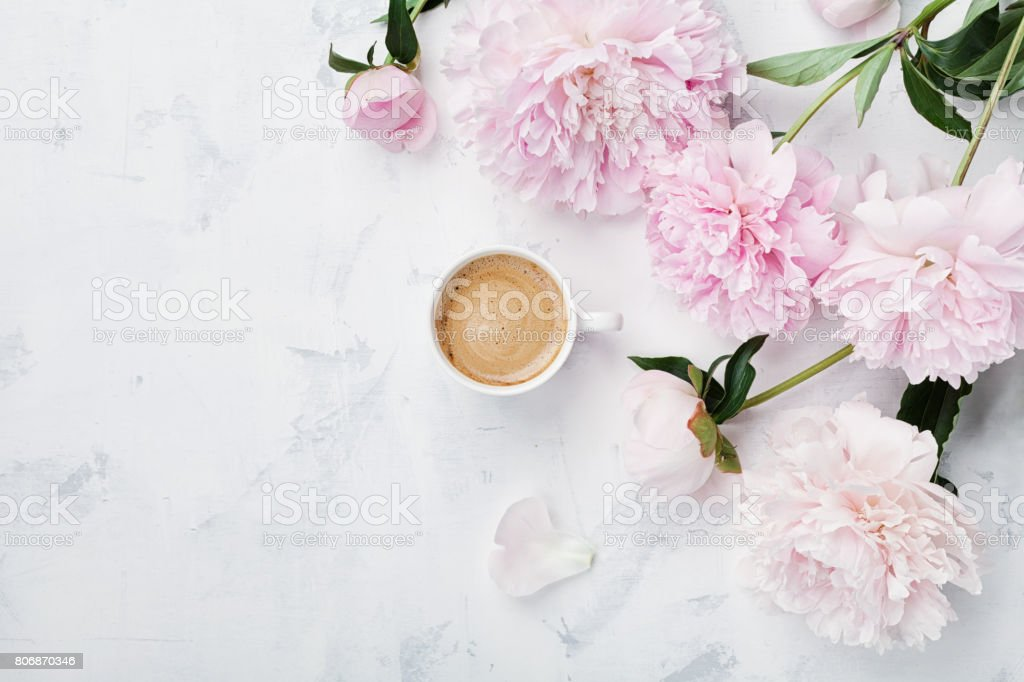 Morning coffee and beautiful pink peony flowers in flat lay style. Cozy breakfast on Mother or Woman day. stock photo